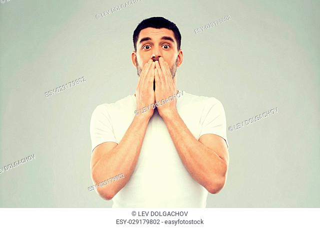 emotion, advertisement and people concept - scared man in white t-shirt over gray background