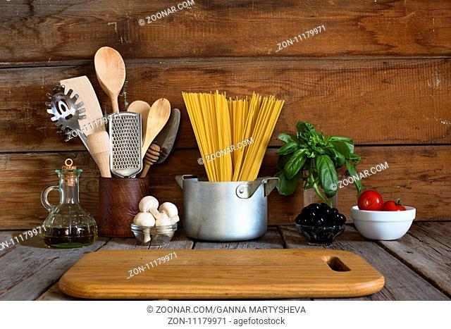 Spaghetti with ingredients for cooking pasta on a wooden background, top view. Concept: home cooking, Fettuccine traditional food