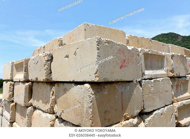 Stack of old concrete blocks against a blue sky