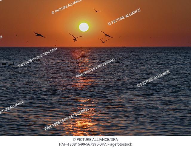 27 July 2018, Denmark, Hvide Sande: Sunset over the North Sea. The small fishing village of Hvide Sande, in the middle of a spectacular dune landscape between...