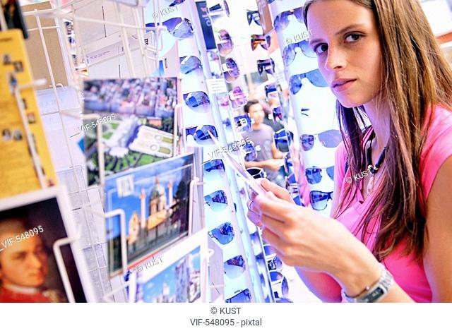 junge Frau betrachtet Ansichtskartenstaender. - Austria, 25/07/2007