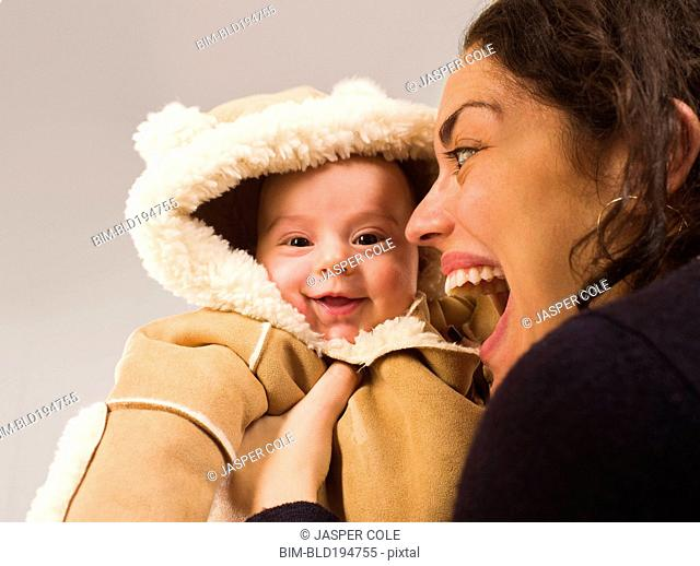 Mother holding newborn baby in winter coat
