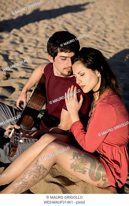 Affectionate couple with a guitar sitting on the beach