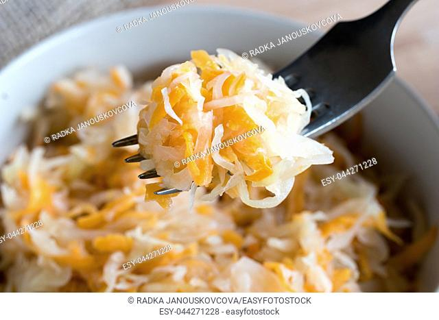 Fermented cabbage and carrots on a fork above a bowl of fermented vegetables