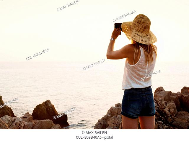 Rear view of woman looking at sea with binoculars, Ciutadella, Menorca, Spain
