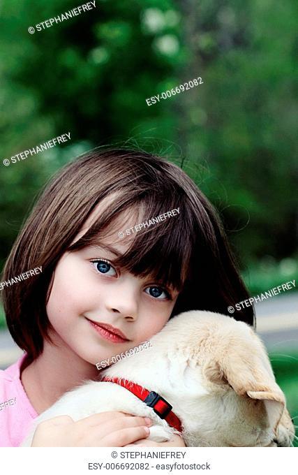 Little girl holding her puppy, an English Cream Labrador Golden retriever mix