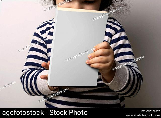 Little girl holding a novel book with blank cover in front of body, editable psd mock up template ready for your design