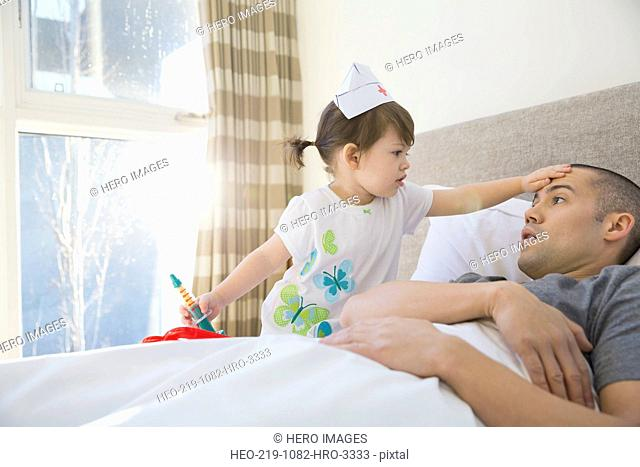 Daughter playing nurse to father in bed