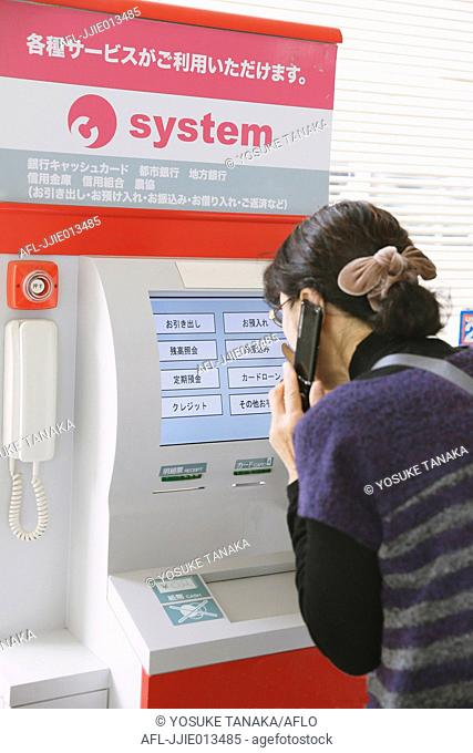 Japanese woman using ATM in a convenience store