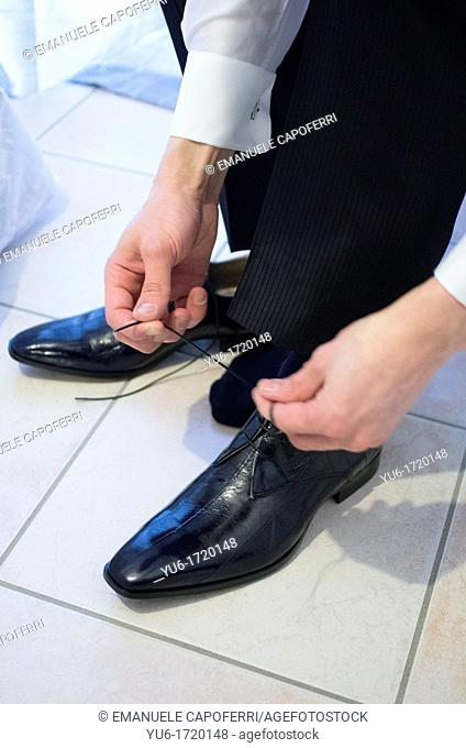 Elegant groom tying his shoes
