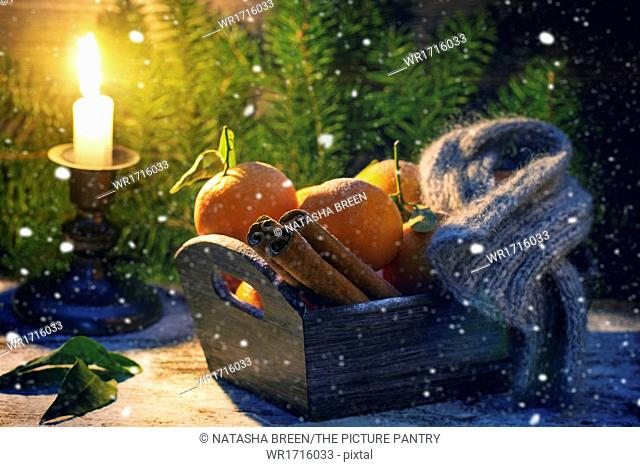 Wooden basket with tangerines, cinnamon sticks and scarf over wooden background with burning candle, snow and Christmas tree