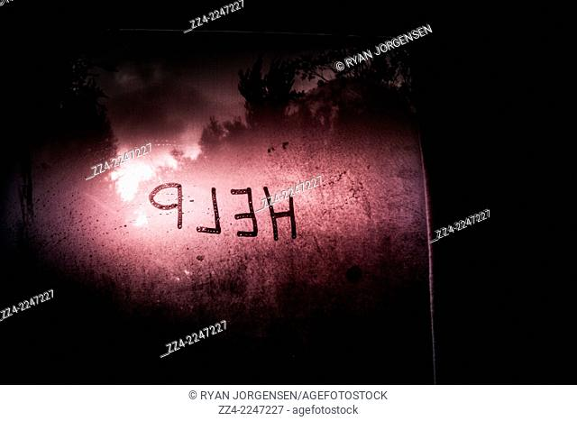 Spooky horror scene of help written on a misty glass window with a red sunrise background. No escape