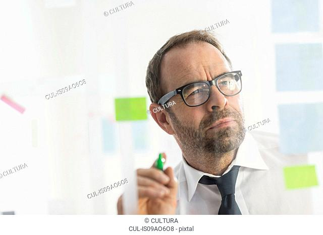 Businessman writing ideas on adhesive notes for glass wall