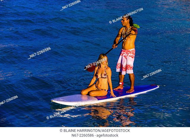 A couple rowing around the lagoon on a paddleboard, Four Seasons Resort Bora Bora, French Polynesia