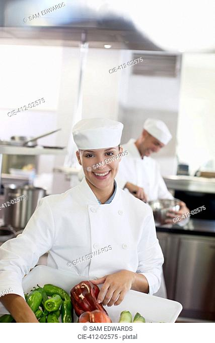 Chef carrying tub of vegetables in restaurant kitchen