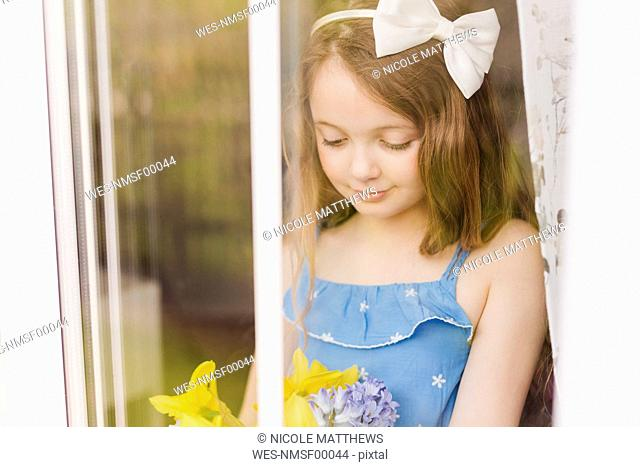 Portrait of smiling girl with cut flowers behind windowpane