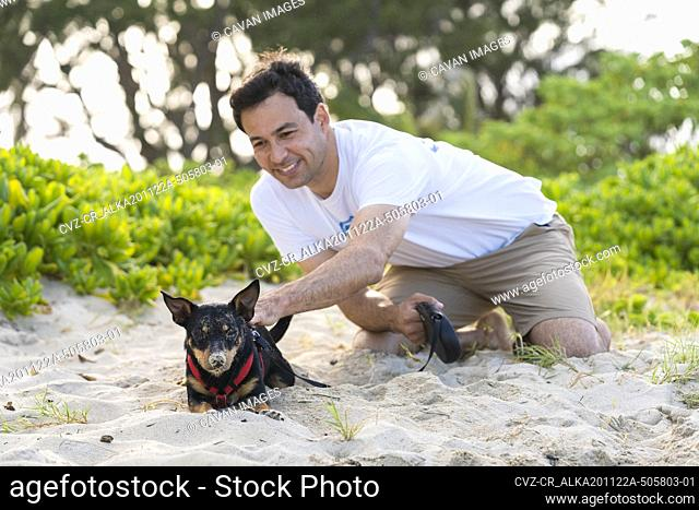 young man kneels to pet black dog covered in sand at the beach