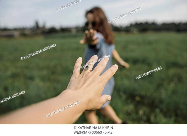Hand reaching out for woman on a field