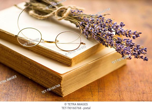Antique book with eyeglasses and lavender