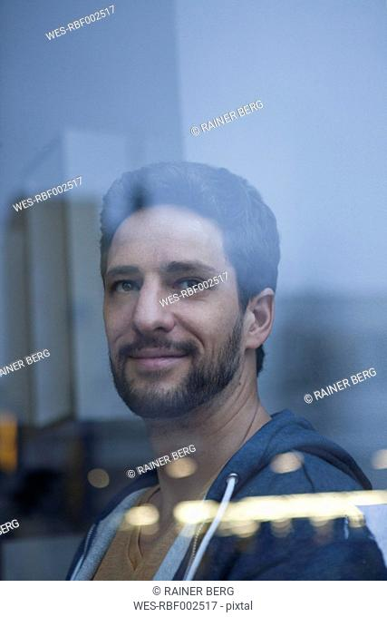 Portrait of smiling man with beard looking through window