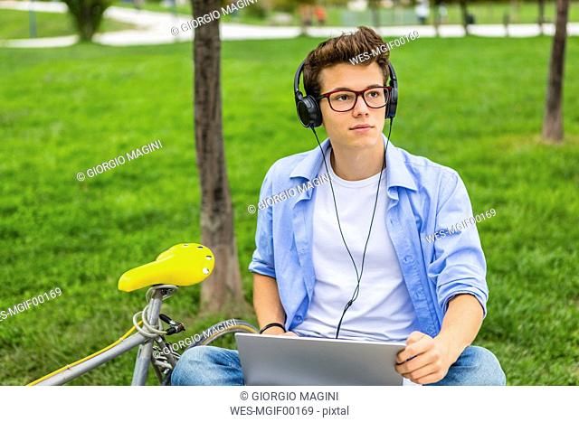 Portrait of serious young man with racing cycle sitting on a bench using laptop and headphones