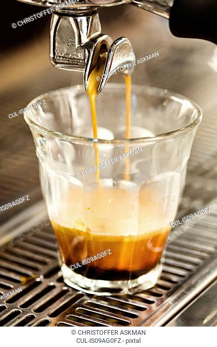 Close up of coffee machine pouring coffee into glass