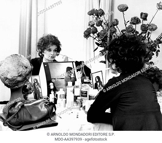 Anna Maria Guarnieri making up. Italian actress Anna Maria Guarnieri, with a cigarette in her mouth, making up in front of the mirror. 1969