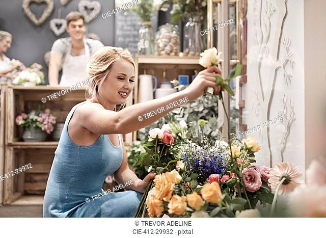 Smiling woman picking out flowers in flower shop