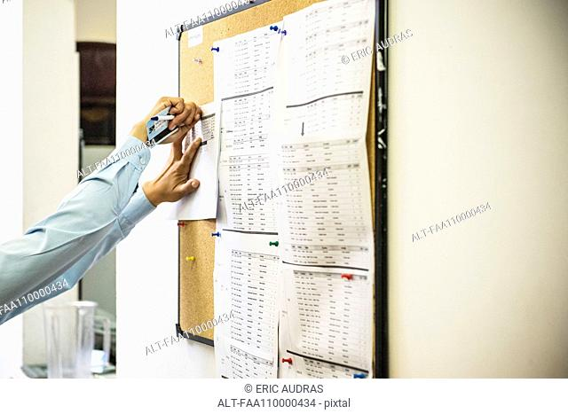 Woman pinning document on office bulletin board