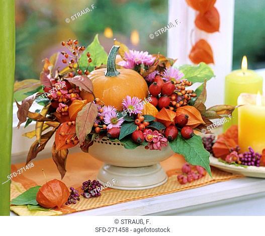 Autumn arrangement in beige metal bowl with pedestal