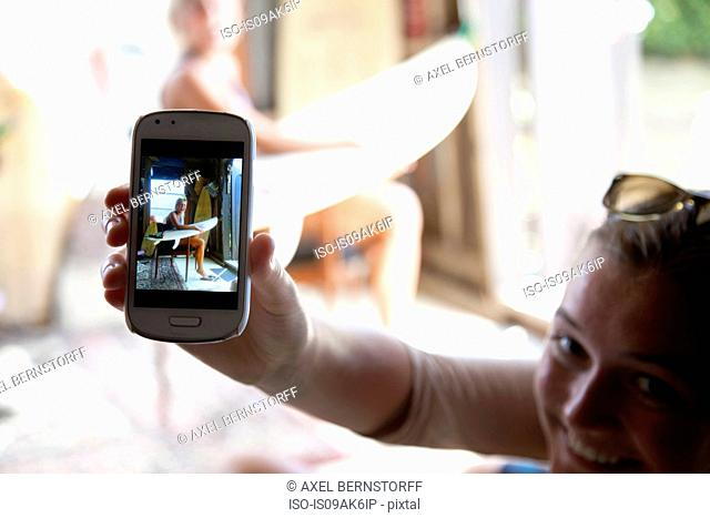 Young woman holding up smartphone with photograph of her best friend