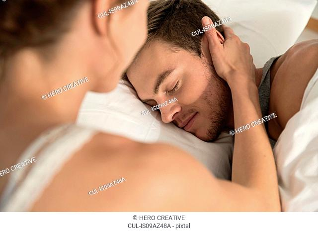 Young woman lying in bed touching sleeping boyfriends cheek