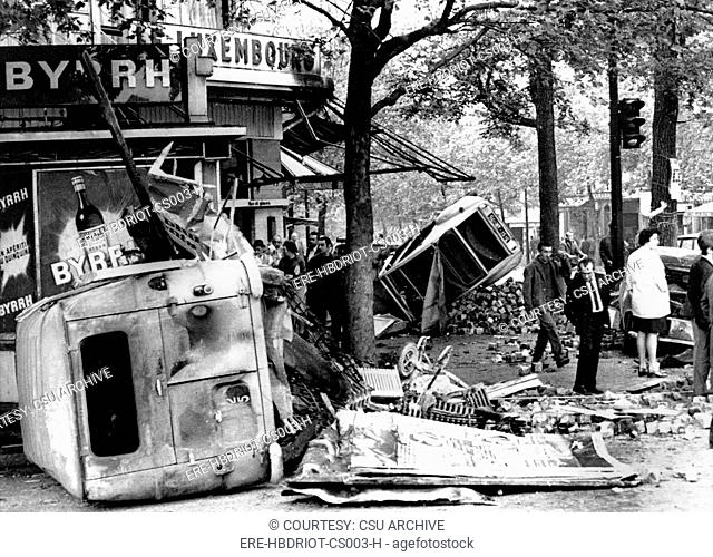 RIOTS-Parisians inspect overturned auto and other debris in the Edmond Rostand Square after riot. 5/25/98