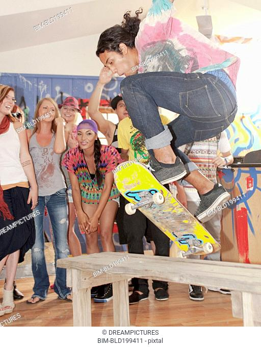 Friends watching man on skateboard at party