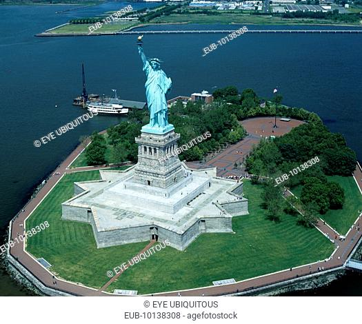 Statue of Liberty. Star shaped plinth river with moored island ferry