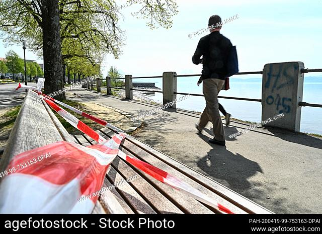 13 March 2020, Baden-Wuerttemberg, Friedrichshafen: Passers-by walk along the riverbank promenade, while the bench in the foreground is blocked by fluttering...