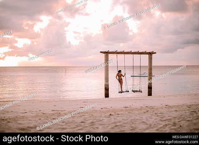 Woman on a swing at the sea at sunset, Maguhdhuvaa Island, Gaafu Dhaalu Atoll, Maldives