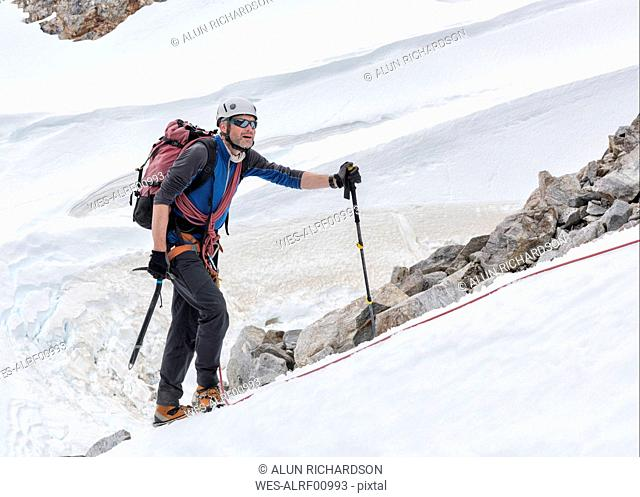 Greenland, Sermersooq, Kulusuk, Schweizerland Alps, mountaineer in snow ascending mountain