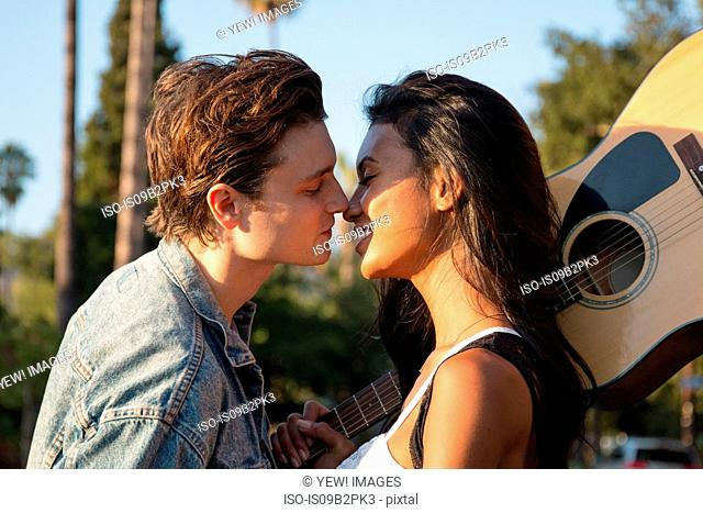 Young couple outdoors, kissing, young woman holding guitar