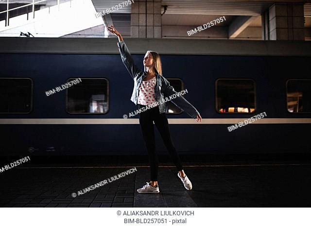 Caucasian woman dancing near train