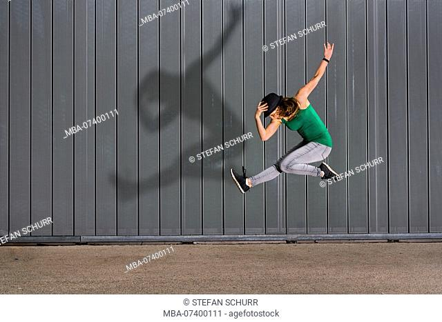 Jumping teenager with silhouette, lifestyle, 18 years old, female, urban environment