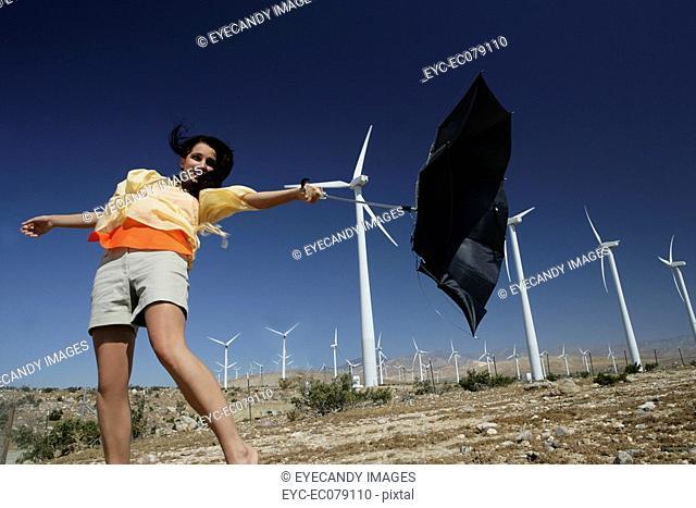 Young woman holding umbrella near wind farm
