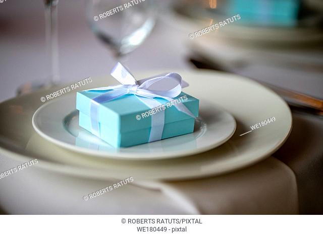 Festive table setting with handmade gift box on plate. Light blue handmade gift box in plate on wedding table