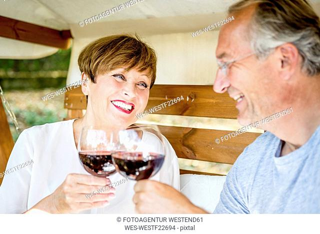Happy senior couple clinking red wine glasses