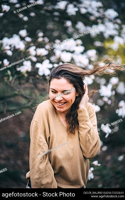 beautiful girl laughs in the park with magnolias
