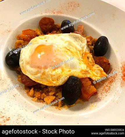 Migas with fried egg, grapes and bacon. Soria, Spain