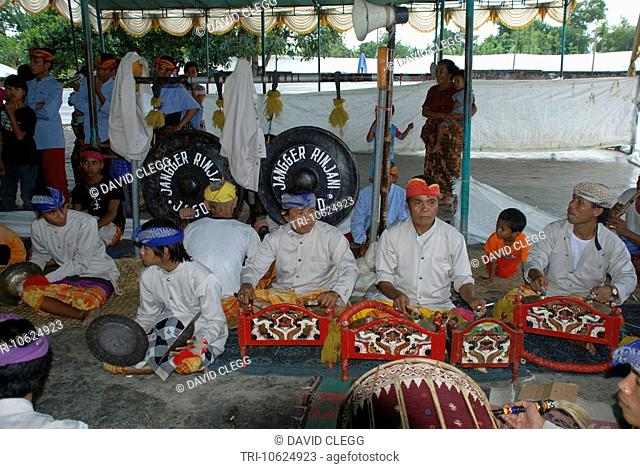 Group of musicians playing the gamalan cymbals drums and the large black hanging gongs at Sasak Muslim wedding ceremony Penujak Lombok Tengah NTB Indonesia