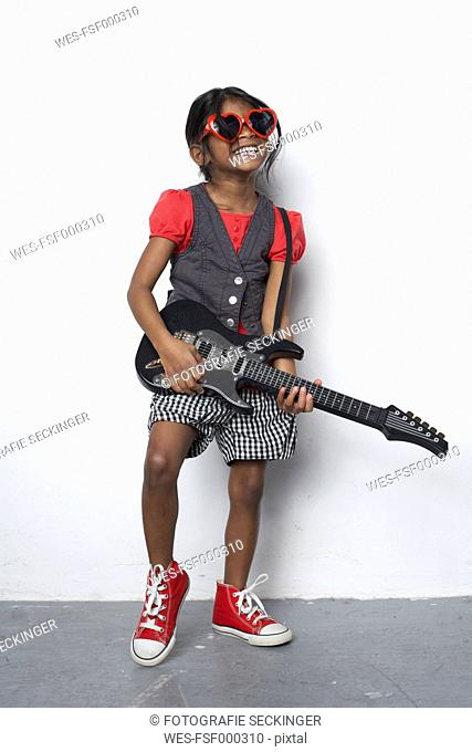Girl with toy guitar wearing red heart-shaped sunglasses