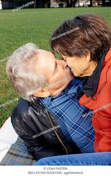 Senior couple kissing in park