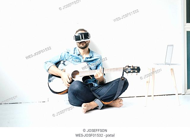 Man with guitar wearing Virtual Reality Glasses sitting on the floor